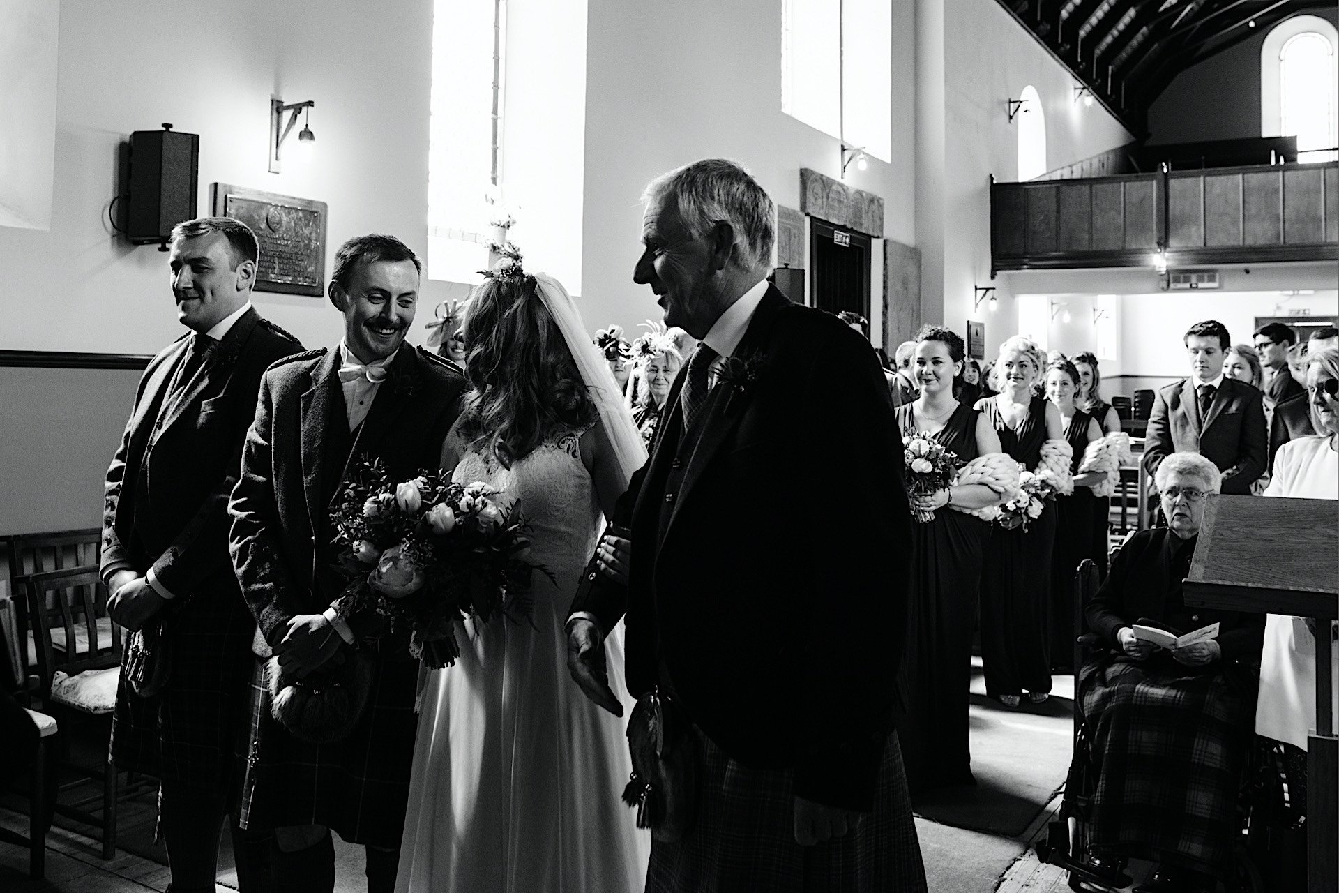bride arriving at top of aisle with father greeting groom groom is smiling
