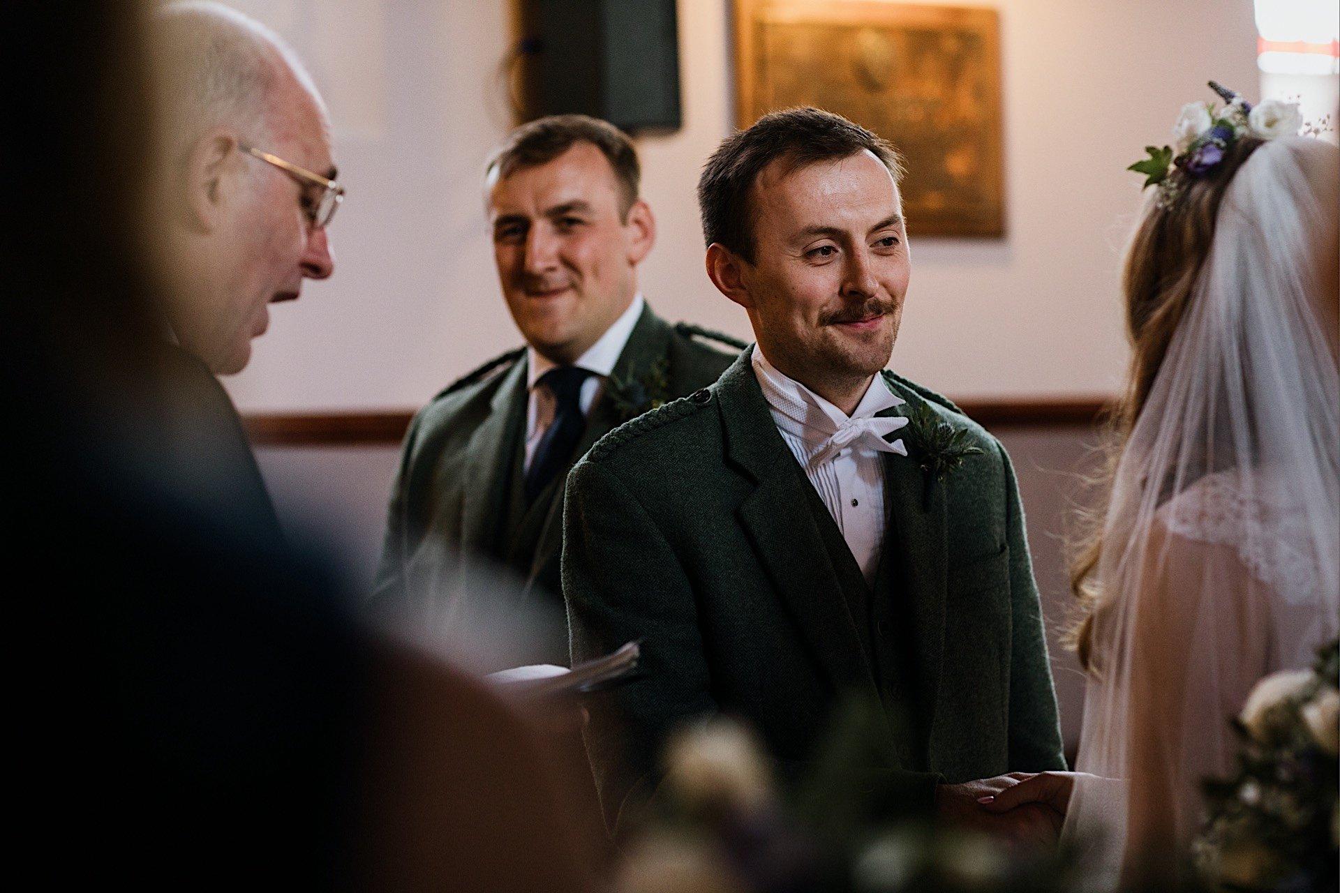 smiling bride in groom facing church