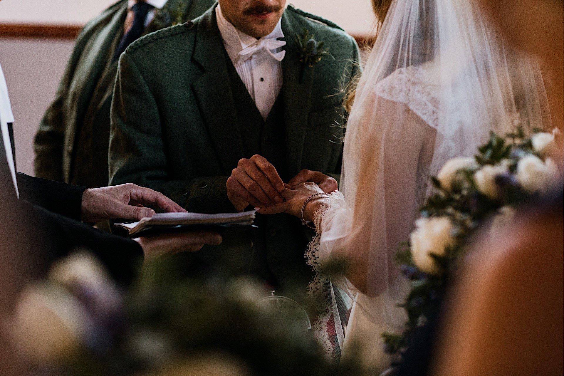 puttting hand Ring groom on brides