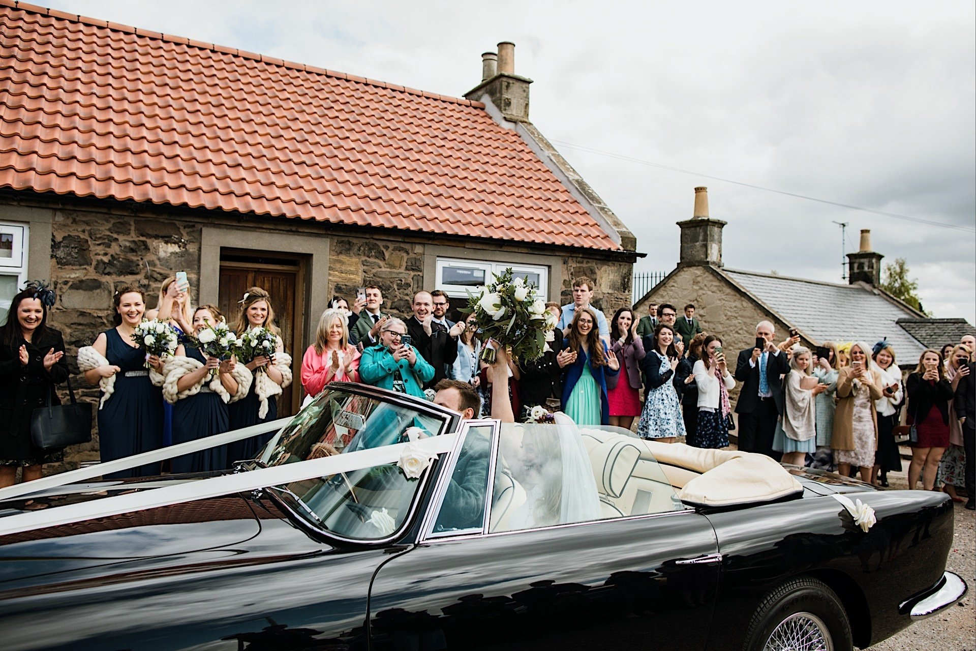 bride has couple in head as guests car cheering above bouquet they off Wedding drive her