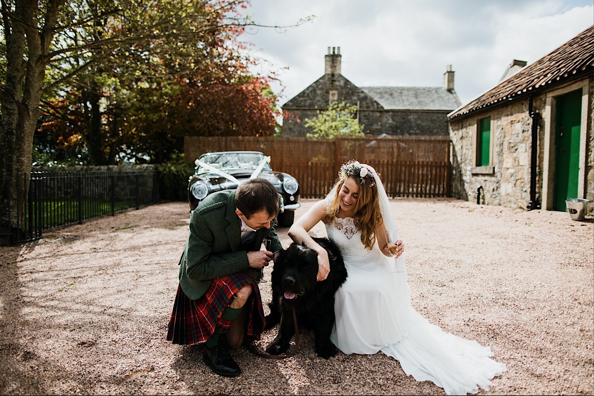 sunny bride and on cuddling day Rhynd the groom dog outside