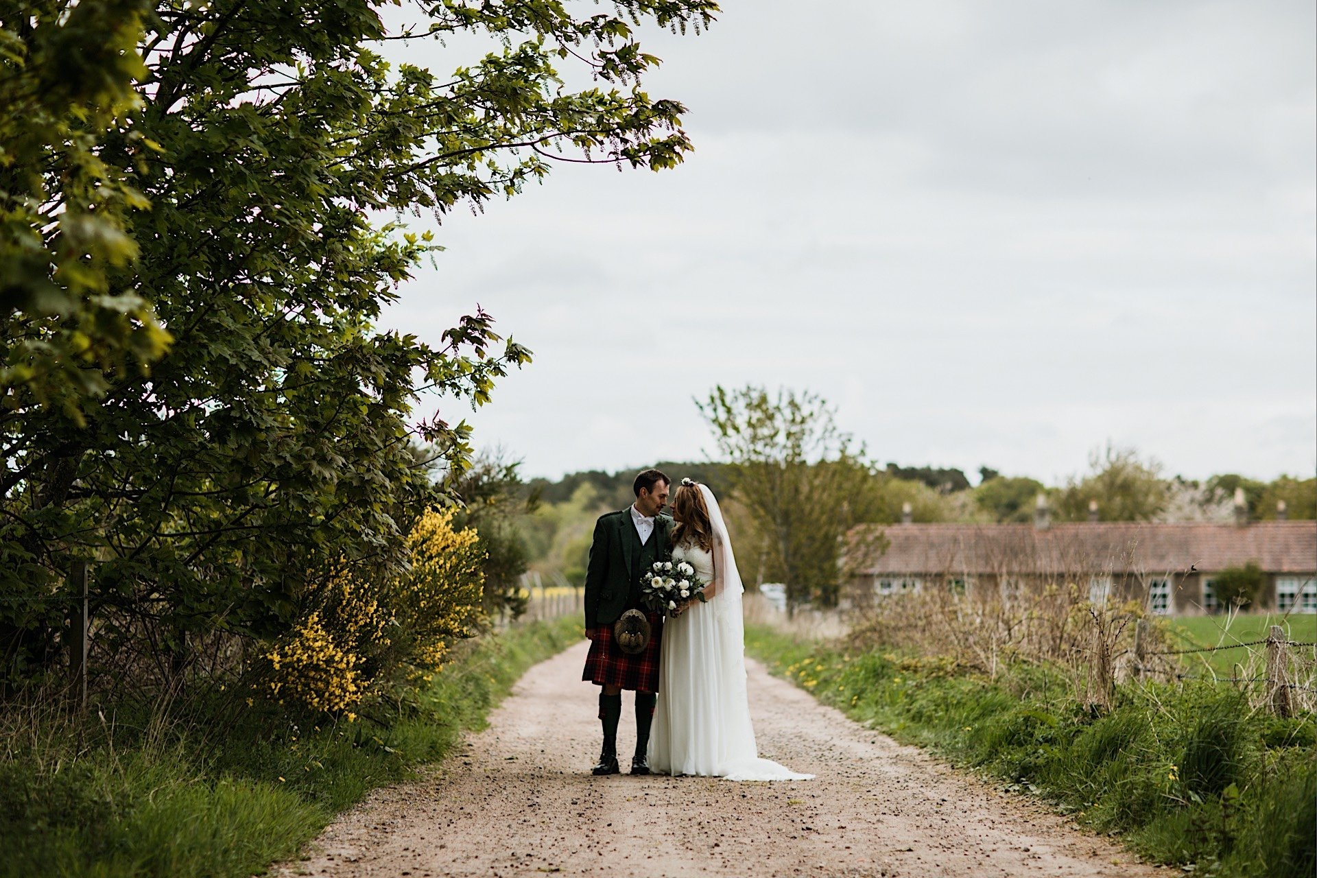 one bride on together country and another lane posed looking groom at