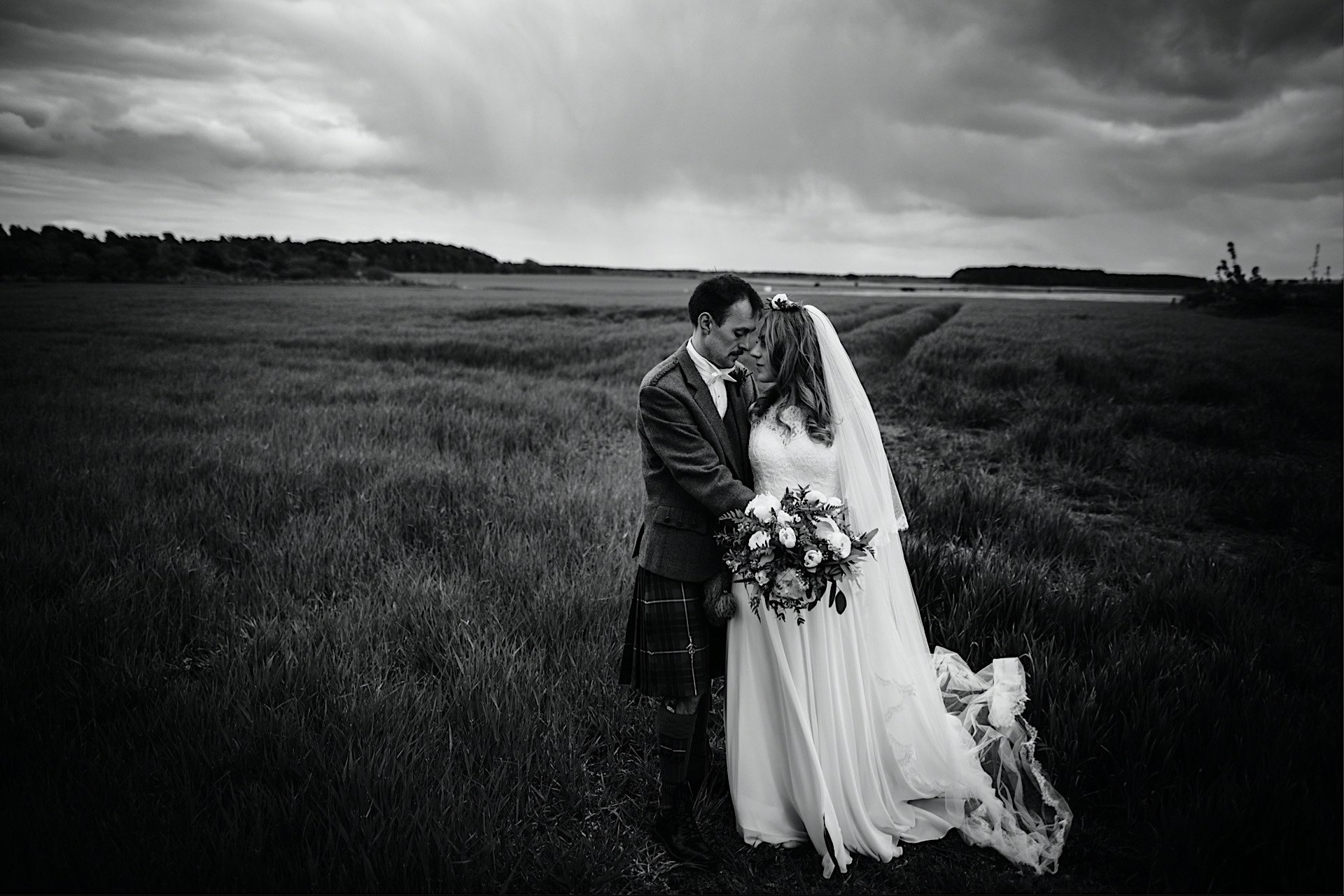one bride facing and another stormy sky With in field groom