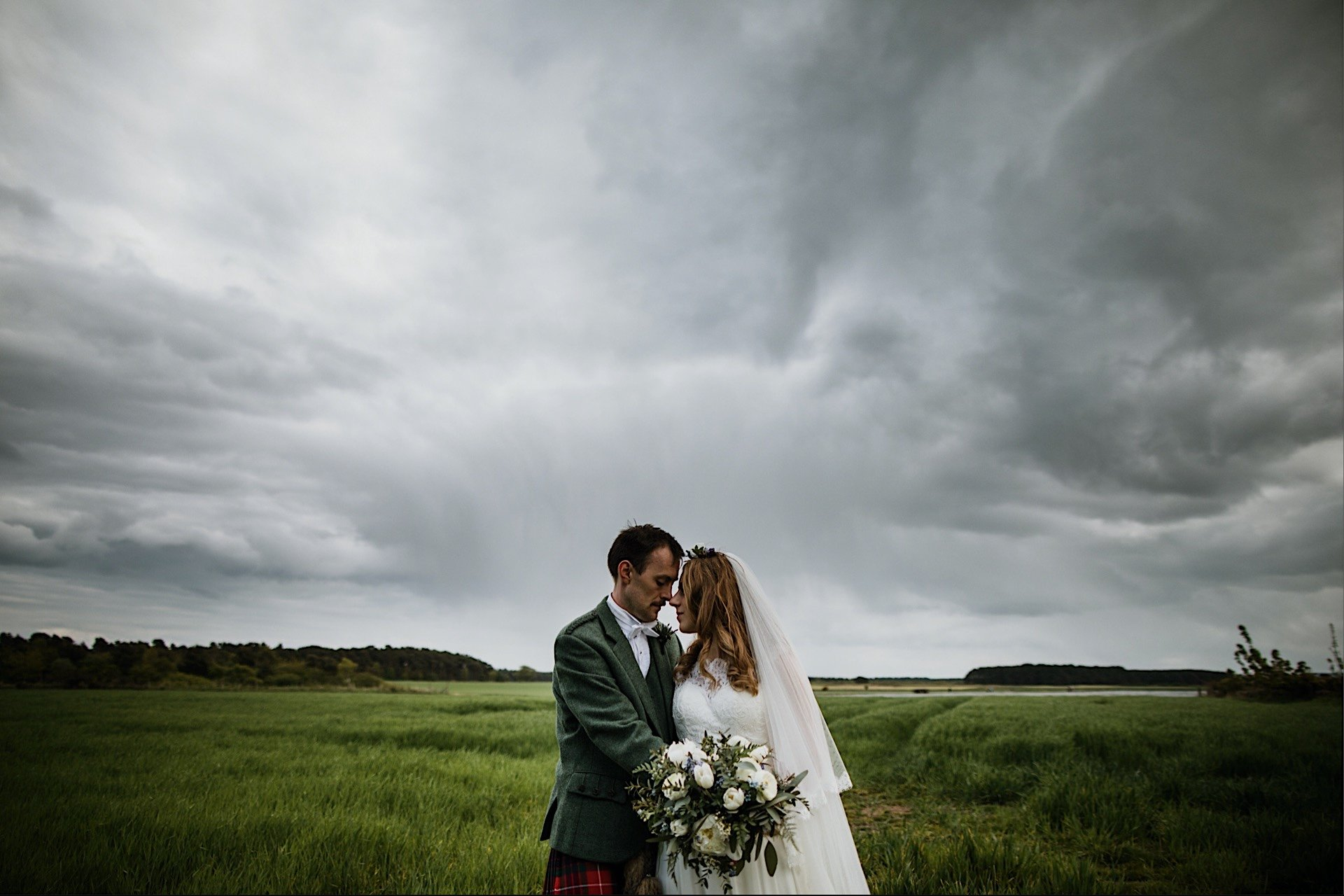 bride anothr grey stormy in facing green behind With field and one them groom sky