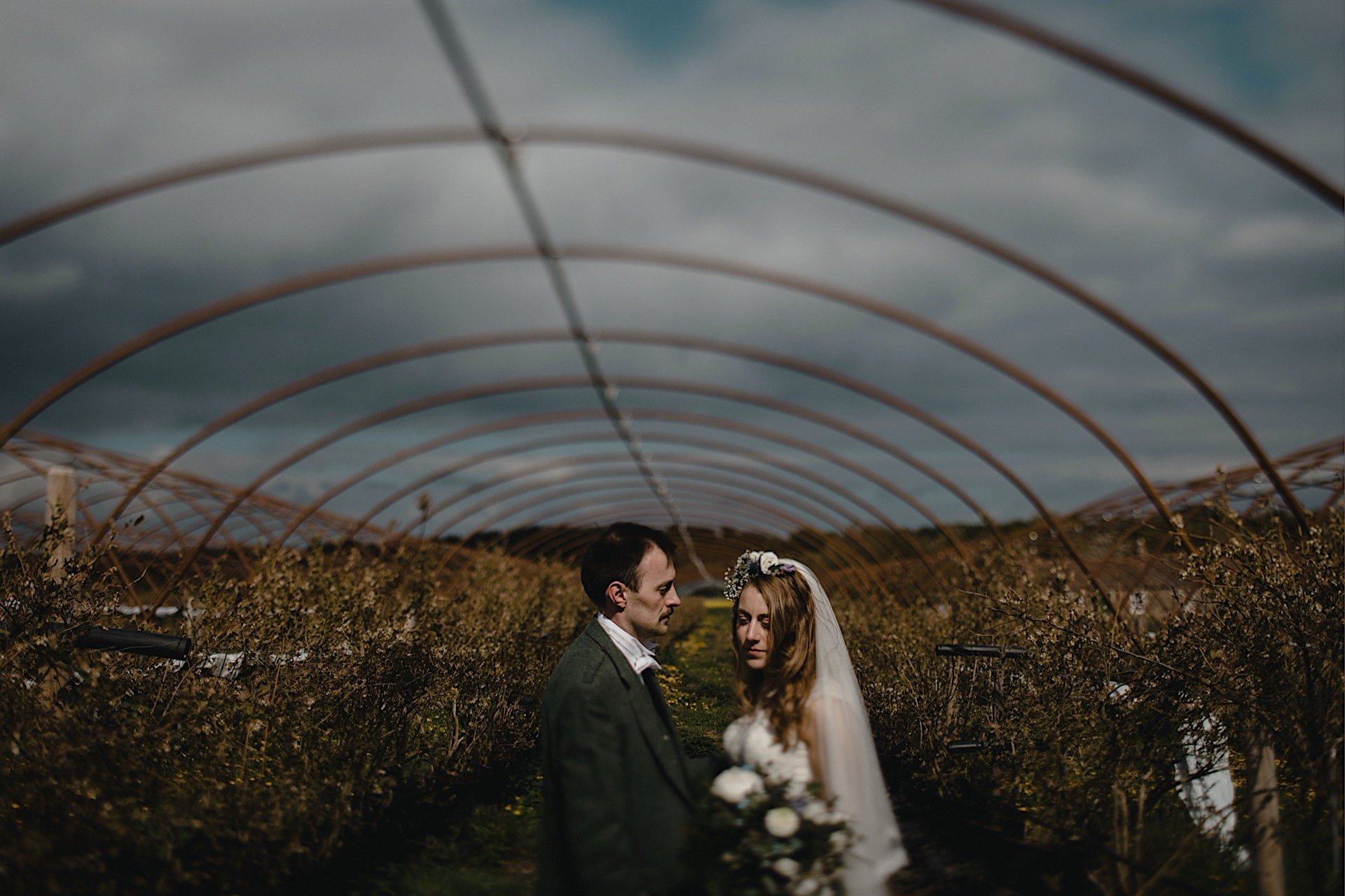 posing bride under facing away from frame Rhynd at the groom polytunnel