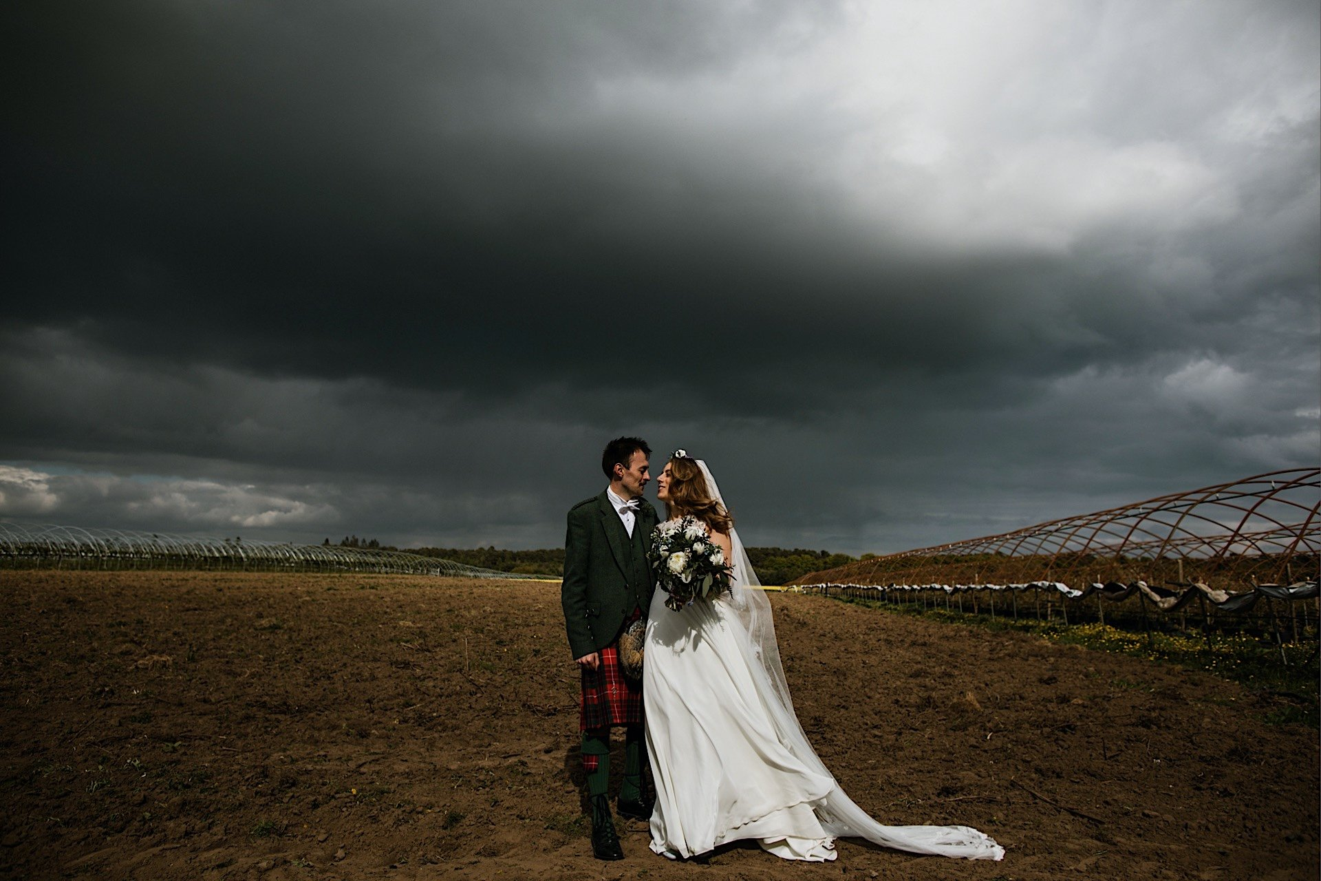 bride posing under empty stormy in bare soil field With and groom sky