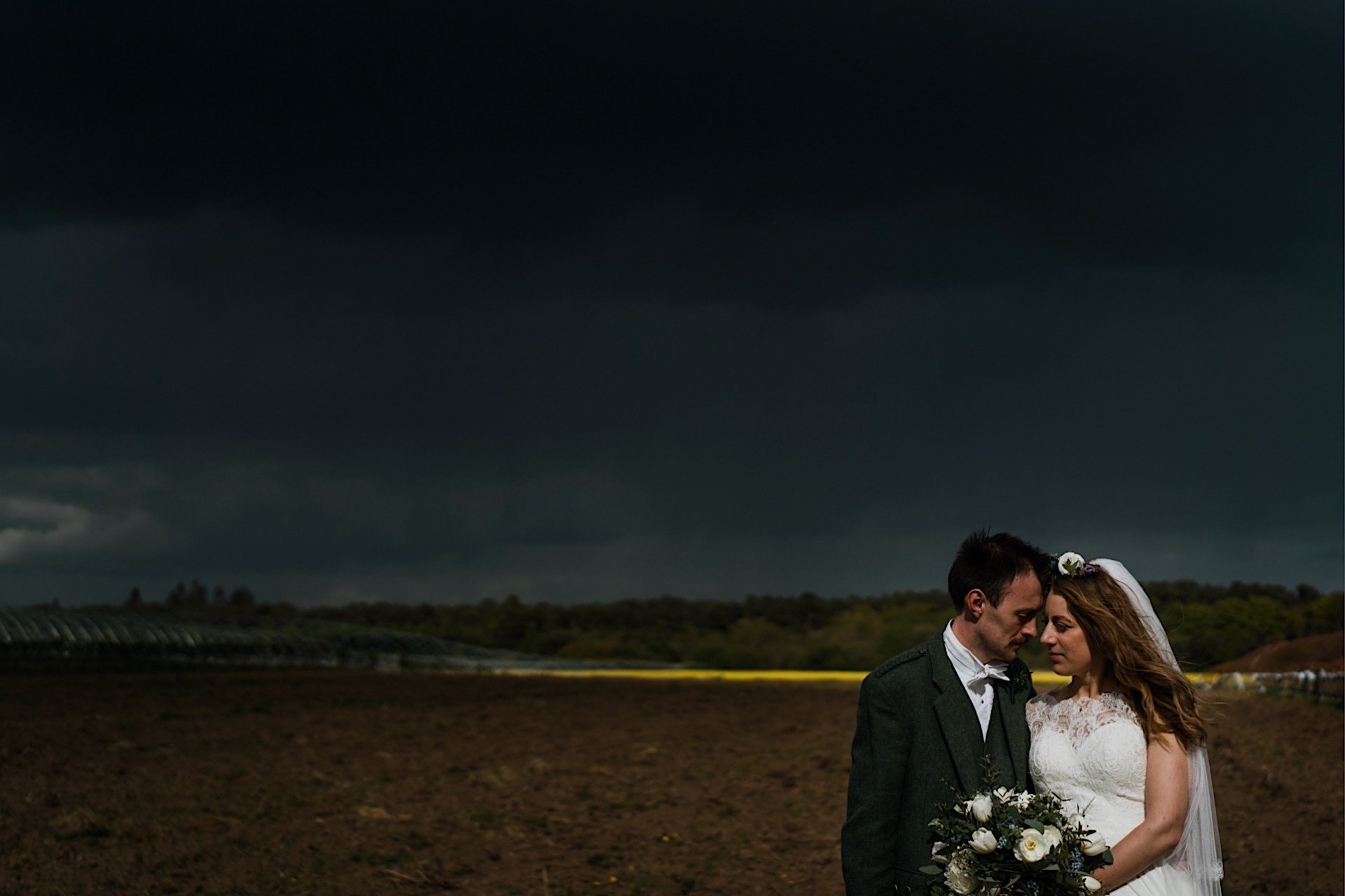 bride stormy in Rapeseed With field closeup of the and distance groom sky