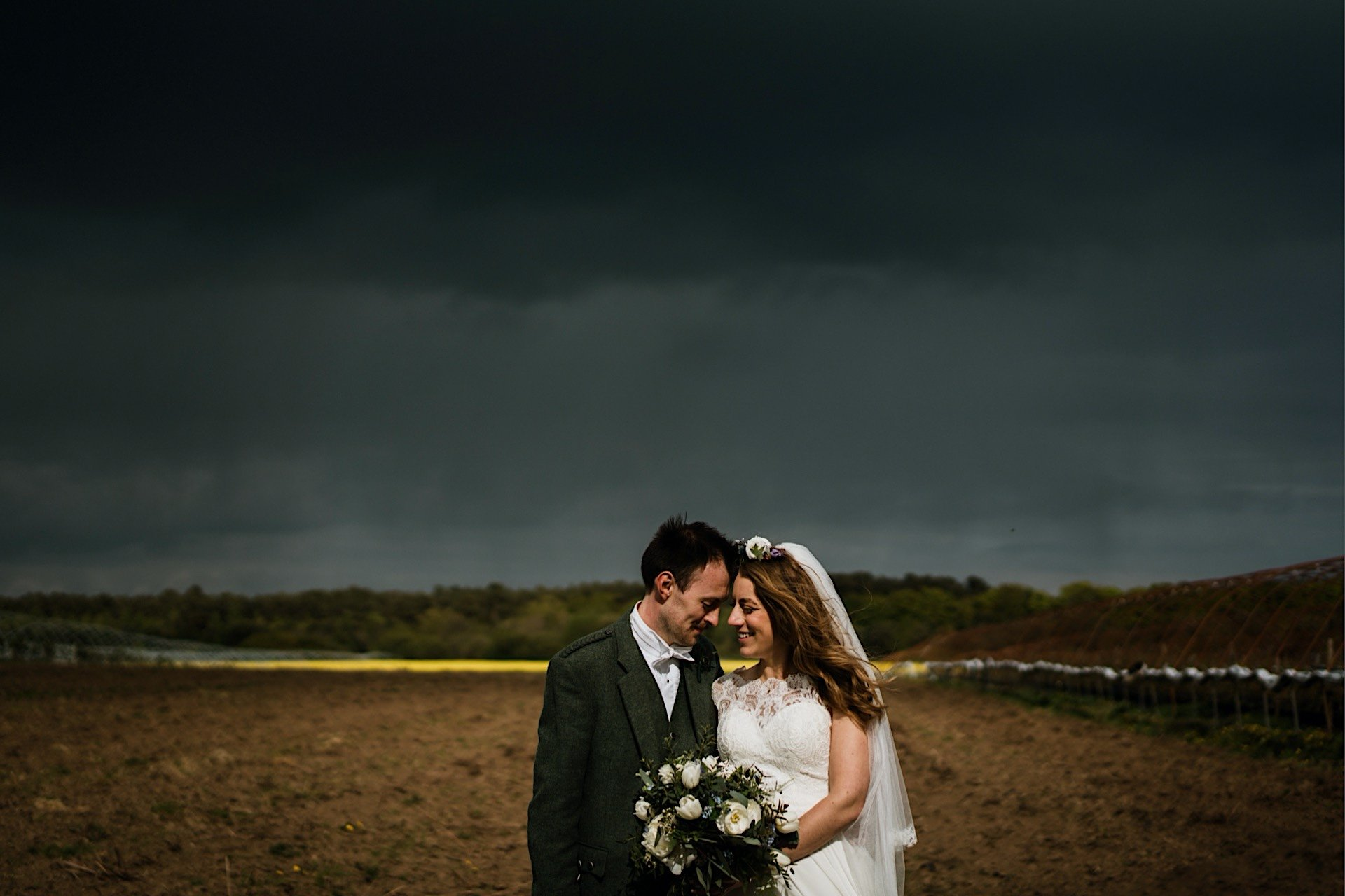 bride blue under stormy in Rapeseed With field yellow closeup background of and groom sky