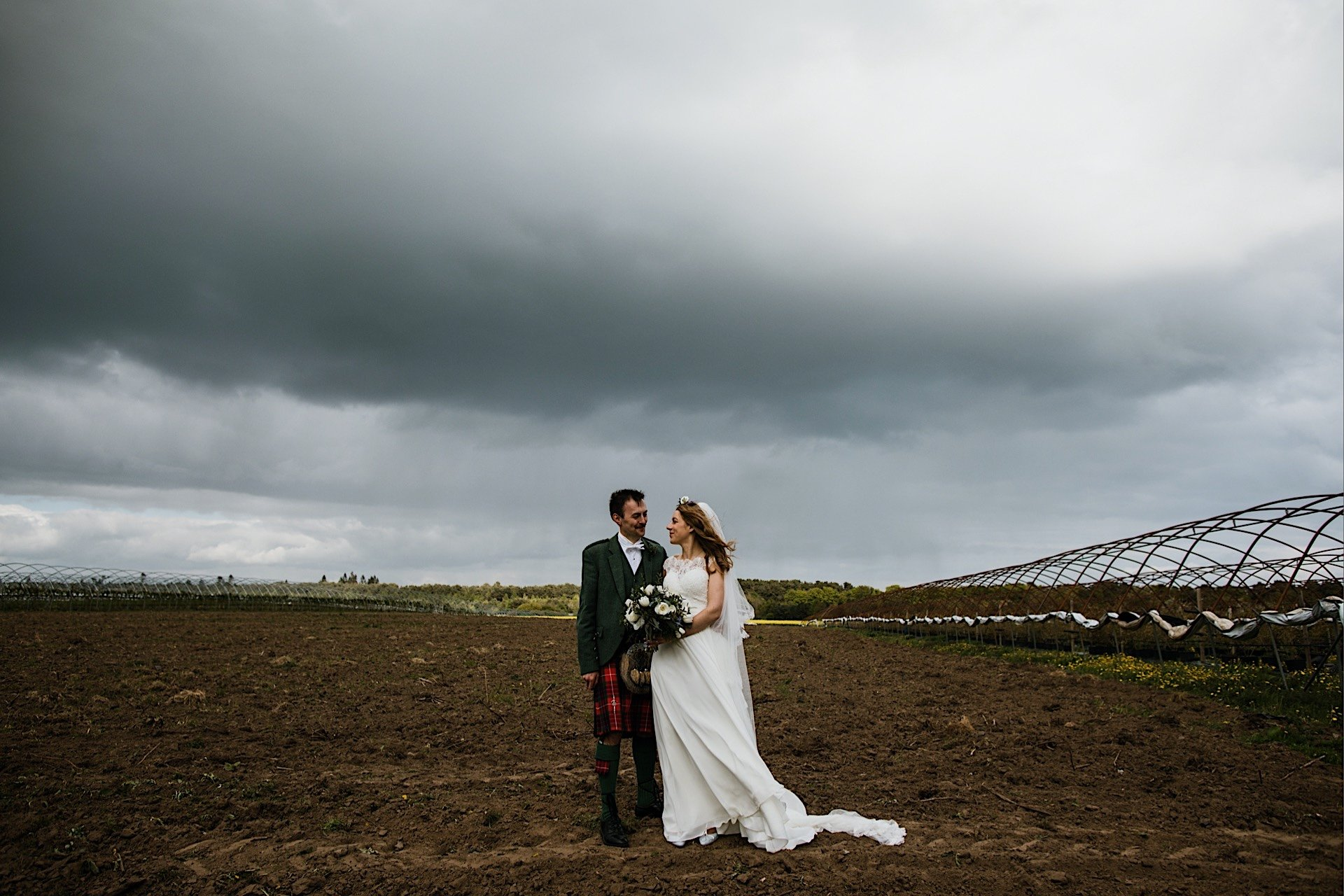 stormy bride in and skies empty With field groom