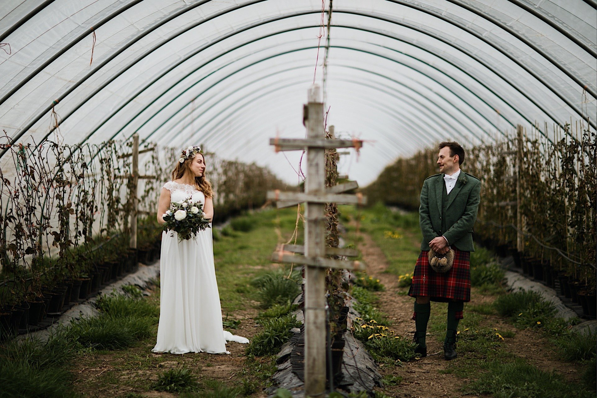 from bride and opposite eachother sides of pollytunnel at looking groom