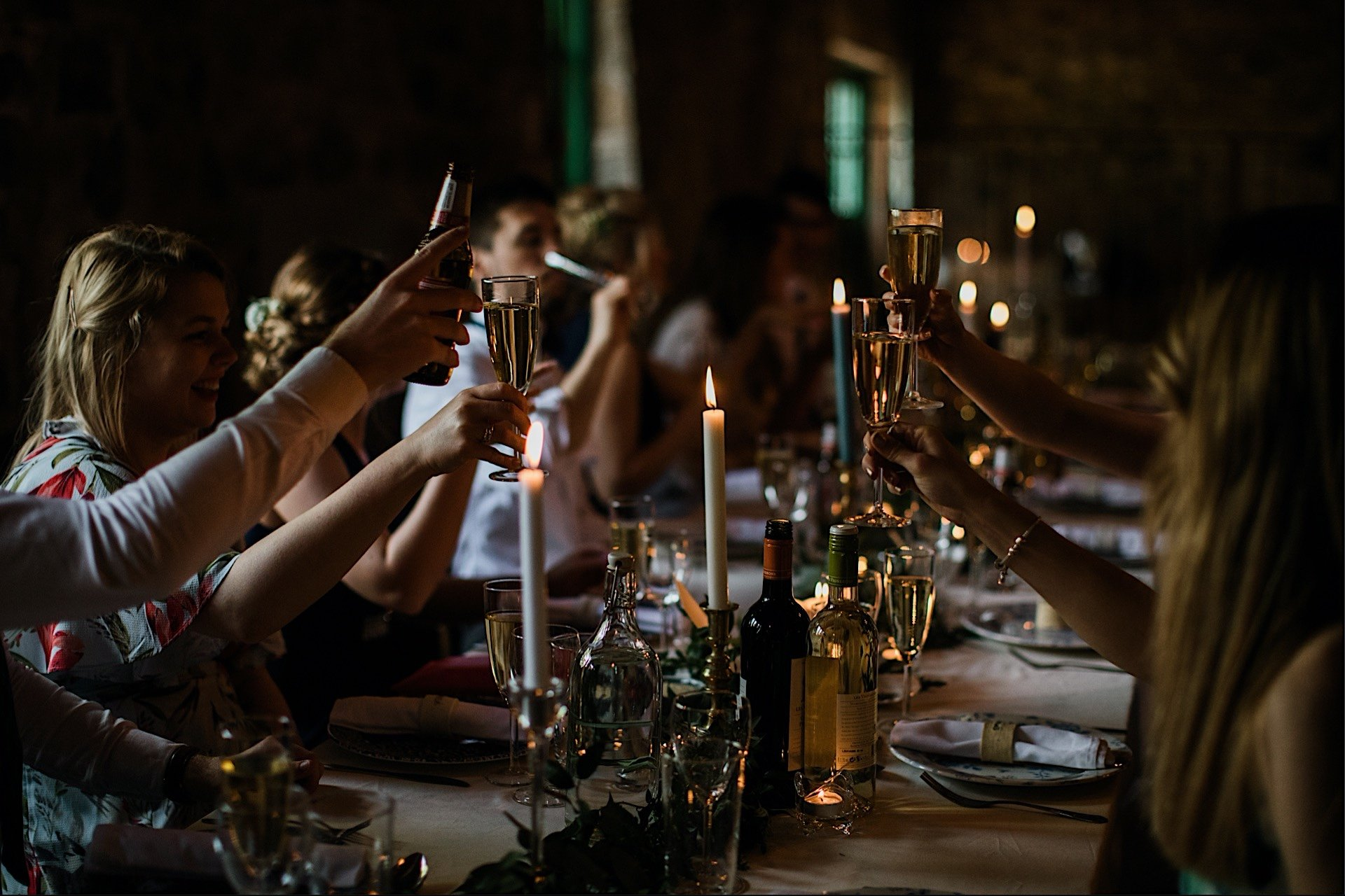 guests toasting flutes by candlelight With at Wedding meal champagne
