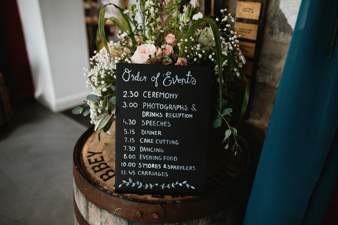 Blackboard with wedding day timeline and wedding start time listing order of events, ceremony time, photographym, speeches, dinner, cake cutting, dancing, evening food, s'mores & spaklers and wedding finish time. Blackboard sits ontop of a whisky barrel at Lindores Abbey Distillery