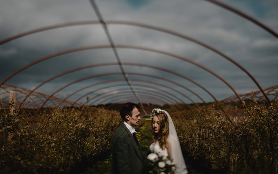bride and groom under pollytunnel frame with stormy skies