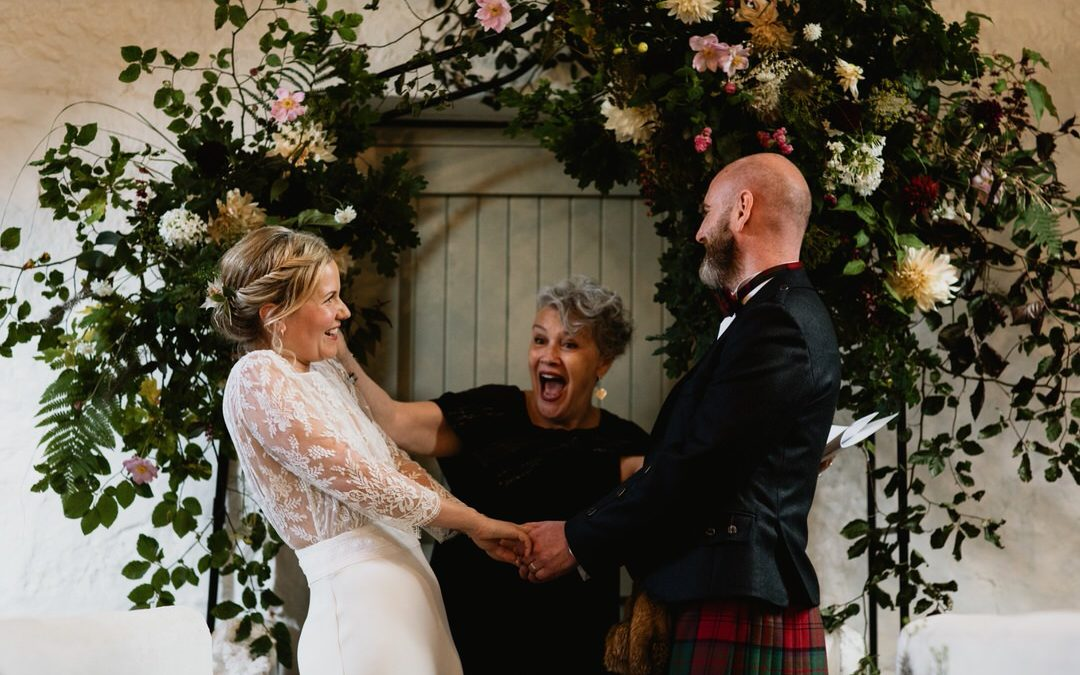 bride and groom under floral arch during wedding ceremony holding hands looking at each other with shock and surprise as they've just been married, celebrant is smiling and looks joyful after announcing they are married
