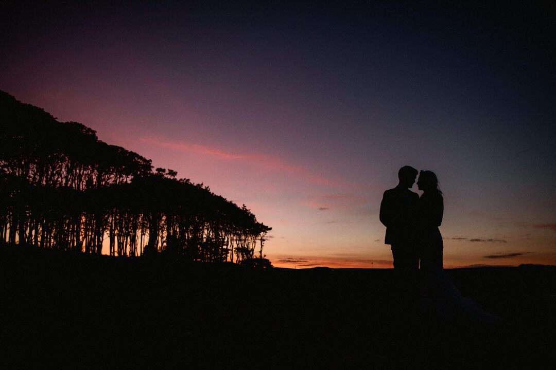 couple silhouetted at sunset with trees in background at the beach on cambo estate where they had their wedding ceremony and reception