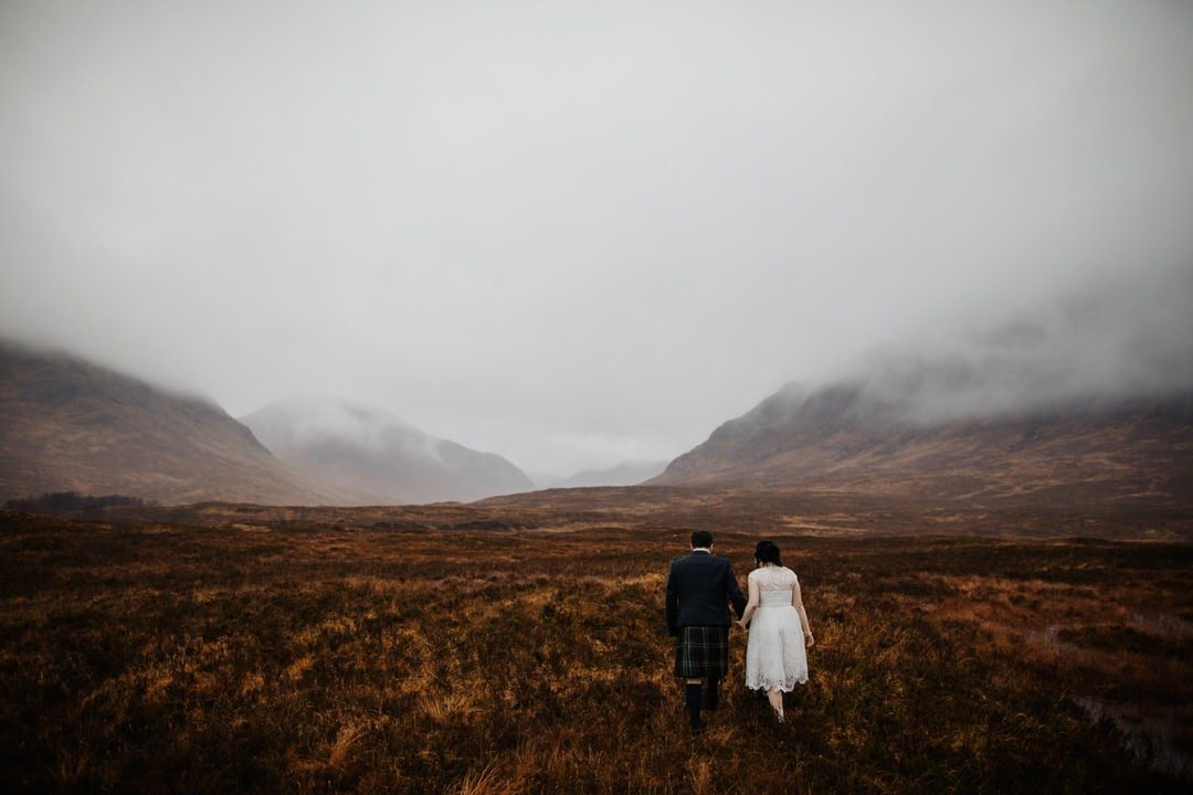 bride and groom walking across a misty field with the hills of Glencoe in the background after their humanist wedding ceremony