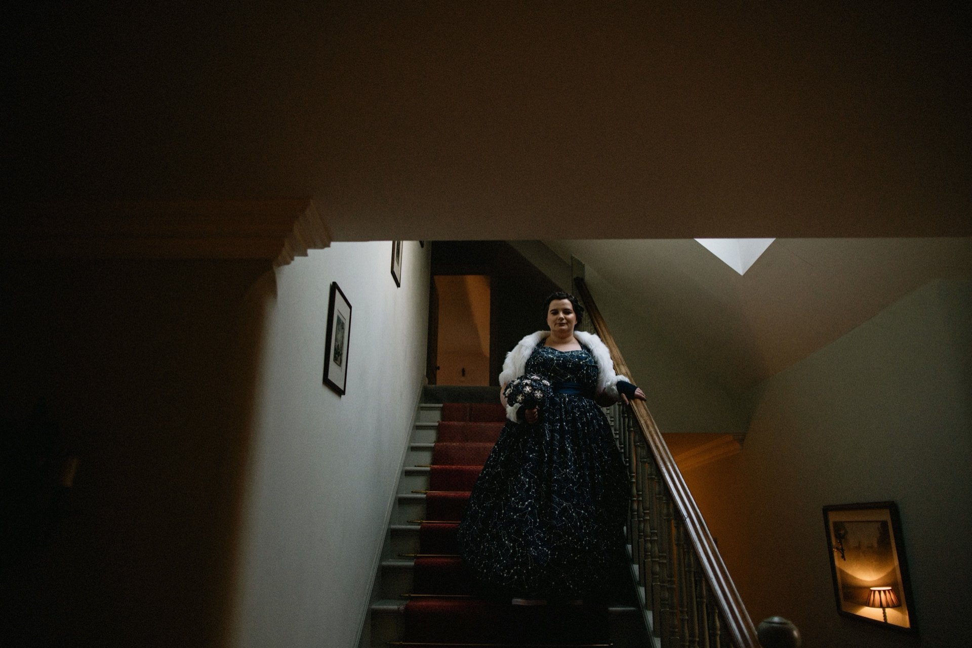 bride wearing constellation dark blue star dress coming down the stairs at craigengillan mansion house for her celestial wedding