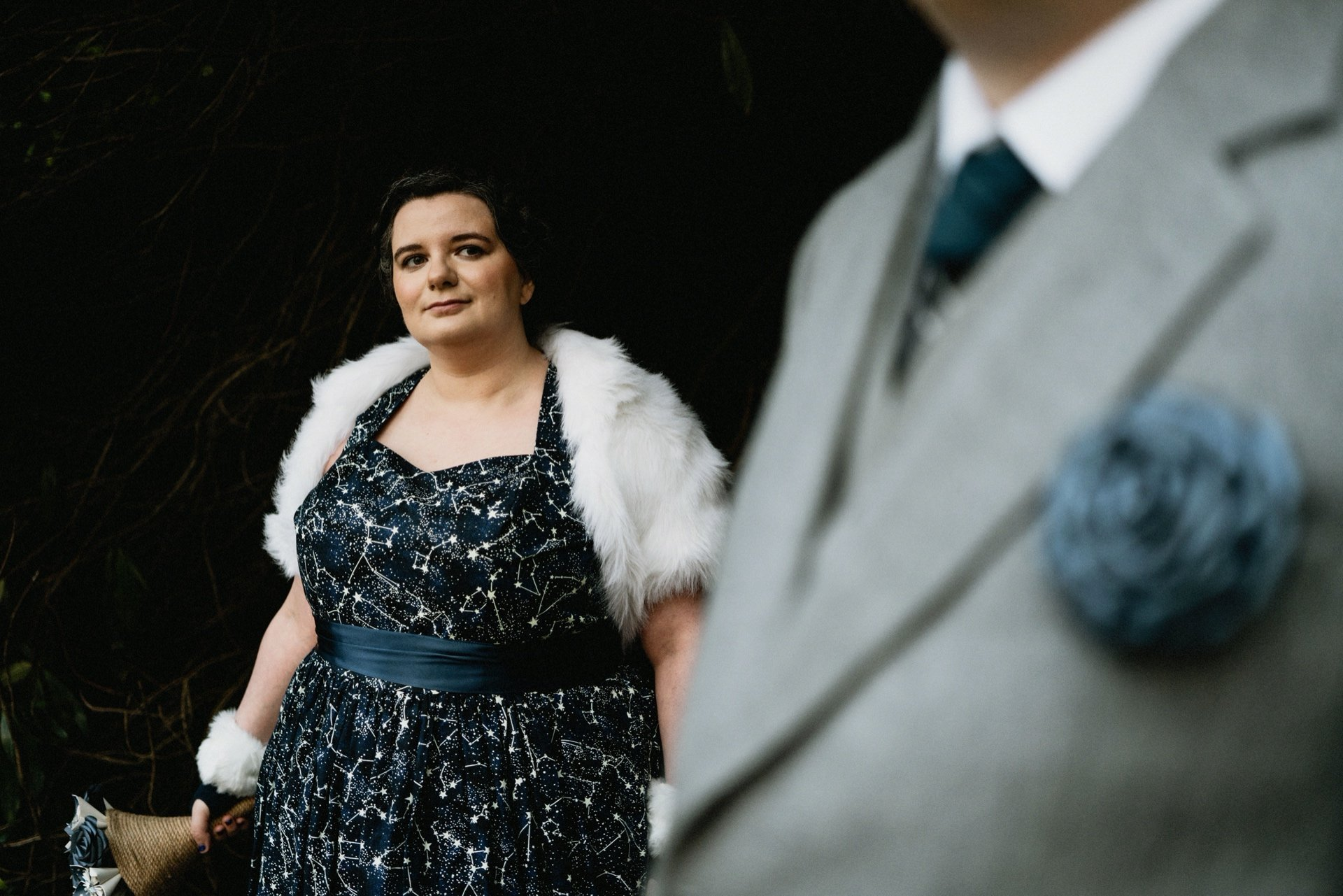 Bride wearing dark blue star print wedding dress and fur shrug looks over to groom