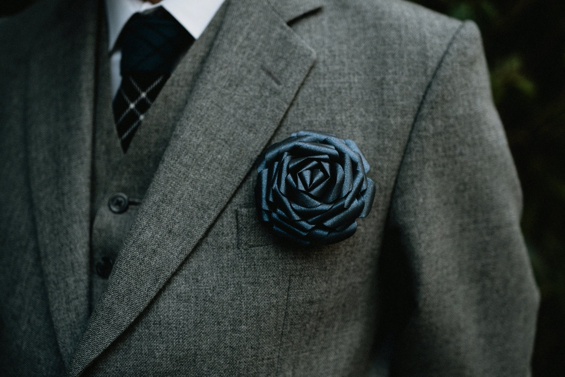 closeup of groom wearing grey suit and dark blue paper rose