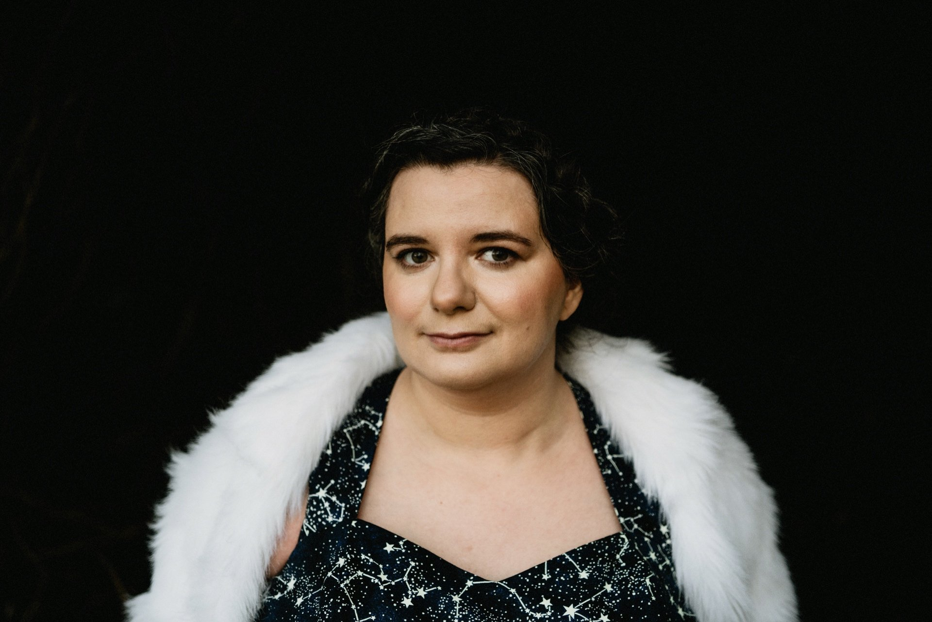 Portrait of bride wearing fur shrug and celestial dark blue wedding dress