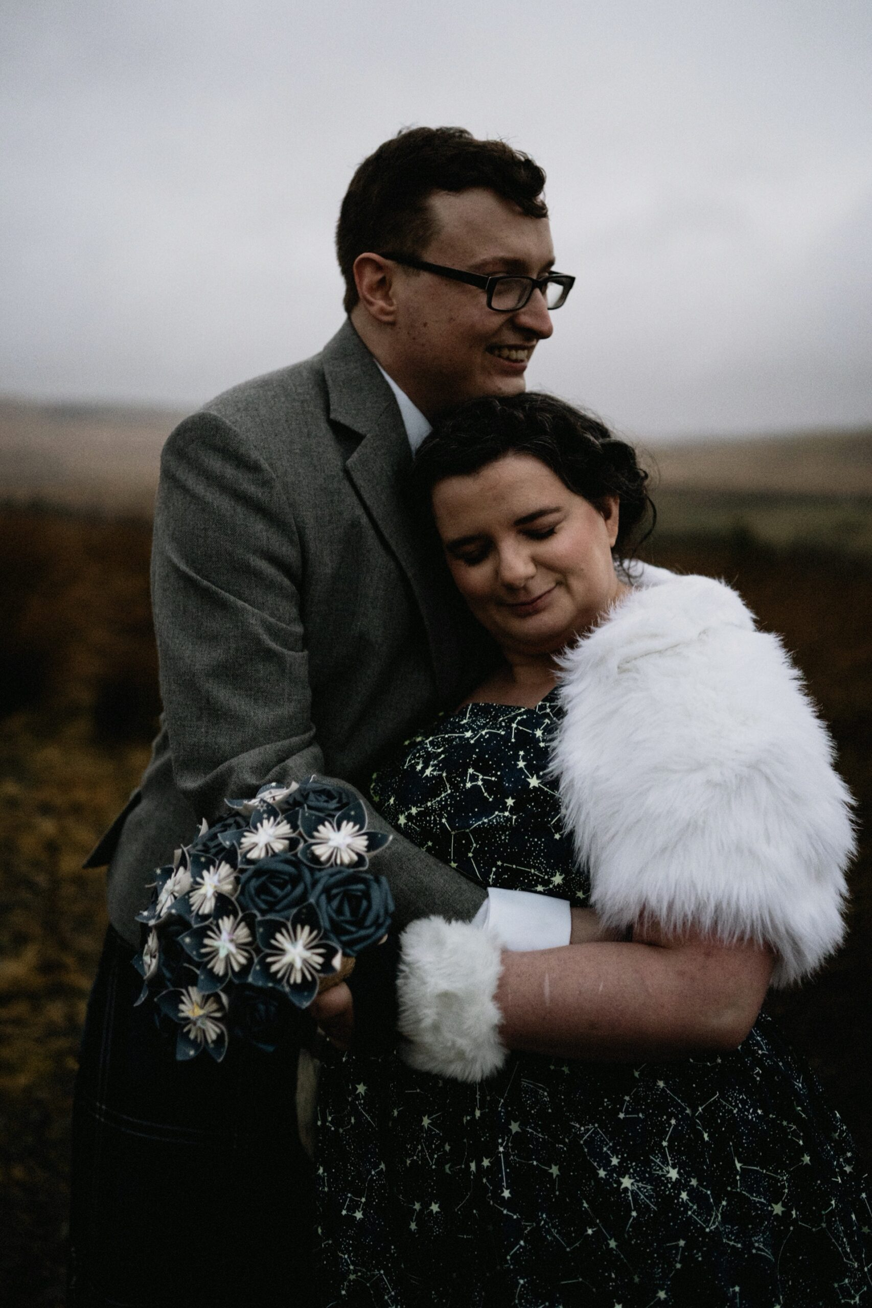 Bride and Groom hug on the moors outside the dark sky observatory.   Bride wears Celestial Wedding Dress with Constellation Stars print, fur shrug and cuffs.
