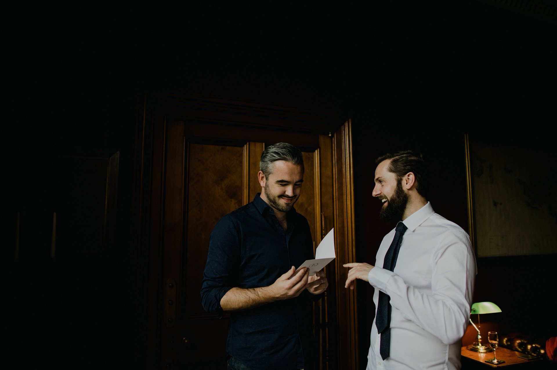groom reading a card with his groomsman