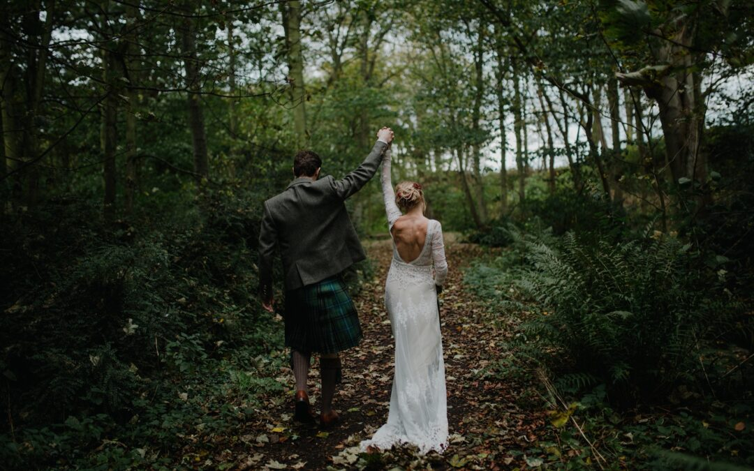 bride and groom hold hands in the air walking through the woodland at cambo estate