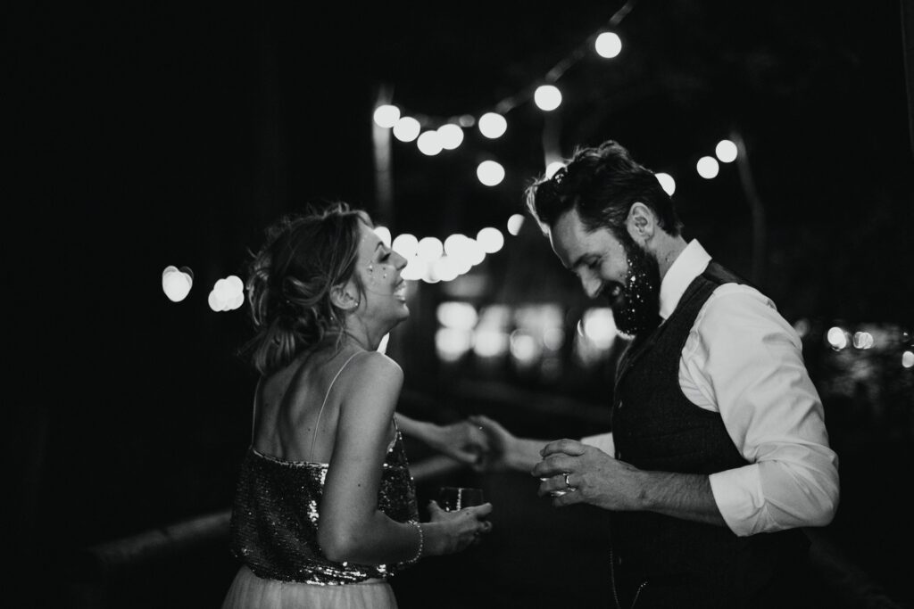 bride and groom dancing at night under the fairy lights