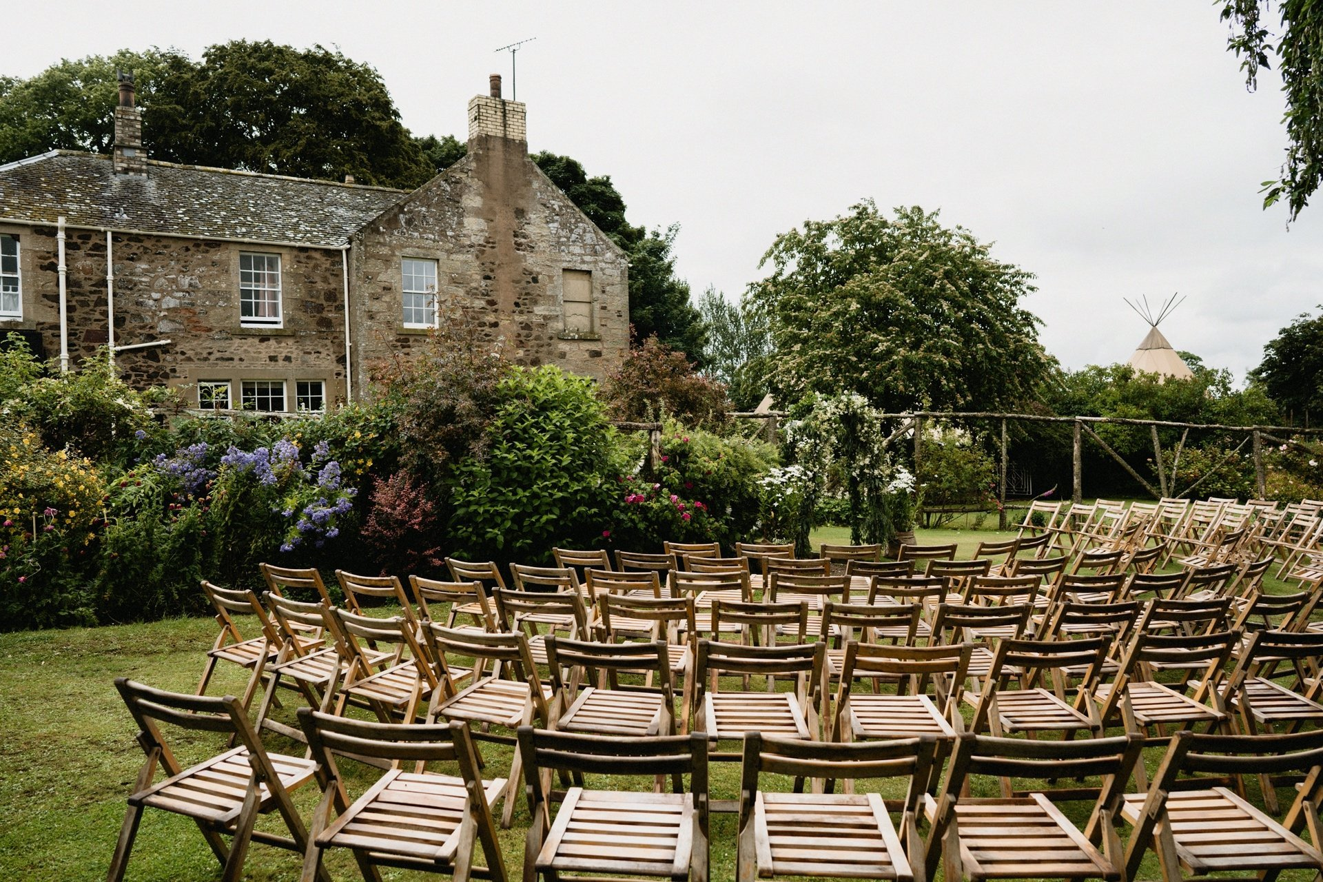Chairs set for a garden ceremony outside a farmhouse with tipi in the background