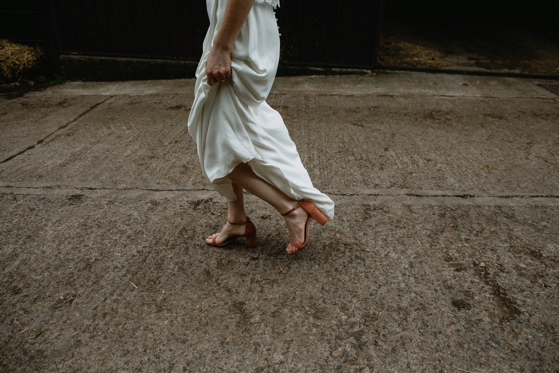 Laure de Sagazan Dress for a farm tipi wedding bride wears pink velvet shoes walking across the farmyard