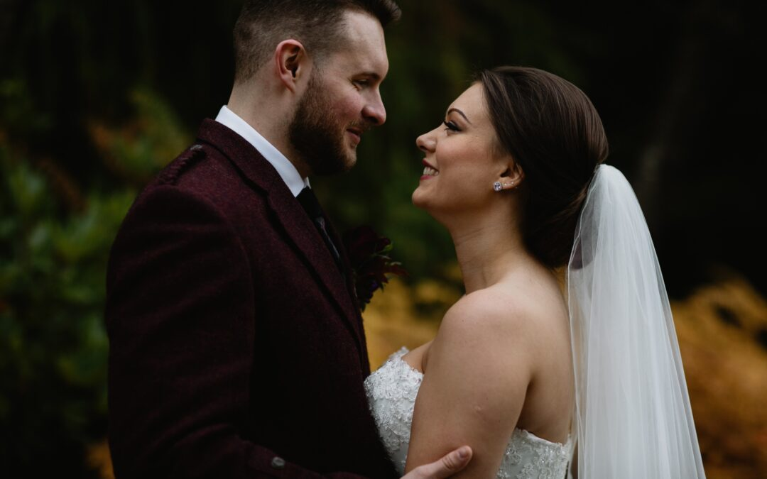 bride and groom at their autumn wedding facing eachother smiling outdoors bride wears a strapless dress and veil, groom wears a burgundy red tweed jacket